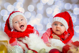 Baby twins in santa costumes for Christmas