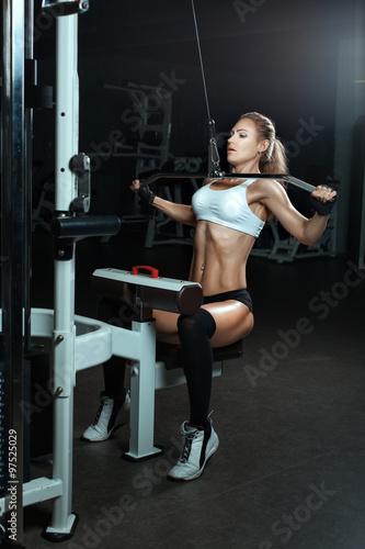 Póster La mujer sacude sus músculos en el simulador en el gimnasio.