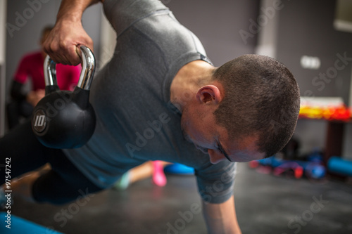 Young man lifting dumbbell and kettlebell at the fitness center Poster