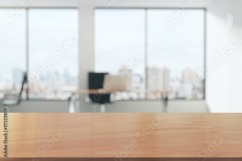Wooden table in light office with panoramic windows