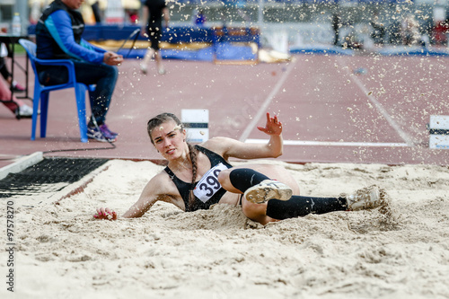Poster beautiful young woman athlete at competitions long jump