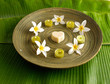 Many white flower with soap, candle in wooden bowl on banana leaf