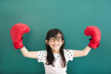 Fototapety happy little girl with red boxing gloves before chalkboard