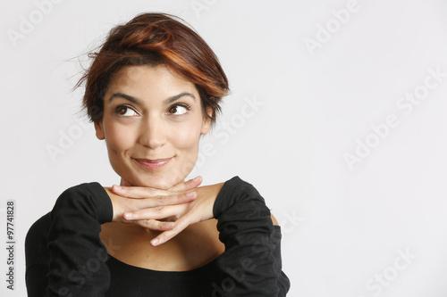 Bellissima ragazza con sguardo sbarazzino incroci le mani sotto il mento Poster