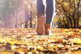 Fototapety Female legs in boots on autumn leaves