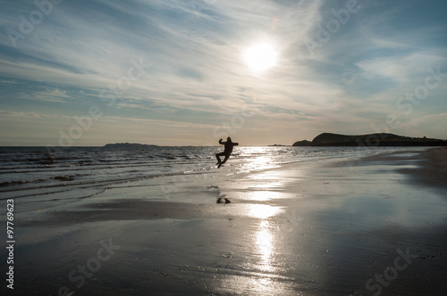 Poster a man doing a heel click jump on the left side at the beach at sunrise