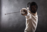 Fototapety Boy wearing white fencing costume and black fencing mask standing with the sword practicing in fencing.