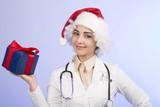 Bella ragazza indossa capello da Babbo Natale, camice da medico, fonendoscopio e tiene in mano un regalo