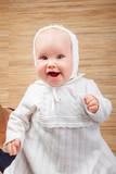 Happy baby in baptismal clothes