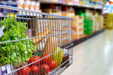 Shopping cart full of food in supermarket aisle side tilt - 97902007