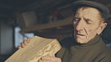 Senior carpenter checking sanded plank in his workshop
