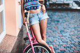 Trendy Hipster Girl with Bike on Urban Background. Modern Youth Lifestyle Concept.