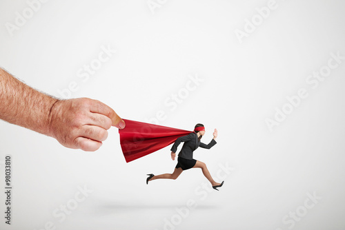 Poster big mans hand holding the red cloak of running superwoman