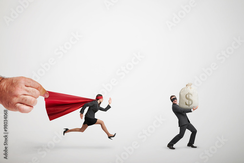 Poster superwoman chasing the thief with big bag of money
