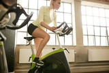 Fototapety Woman working out on gym bike