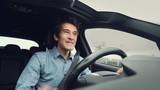 Man exultant full of joy driving car