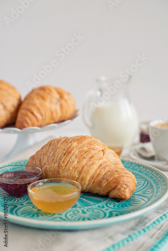 Plakat Romantic breakfast with croissant, coffee, milk, honey and jam on the table