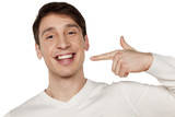 Fototapety smiling young man pointing a finger at his beautiful teeth