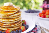 Stack of pancakes with fresh fruit, syrup and butter
