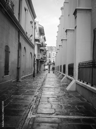 An alleyway in New Orleans French Quarter with lampposts - 98237205