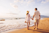 Mature Couple Walking on the Beach at Sunset - 98290667