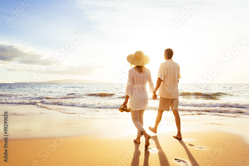 Mature Couple Walking on the Beach at Sunset Poster