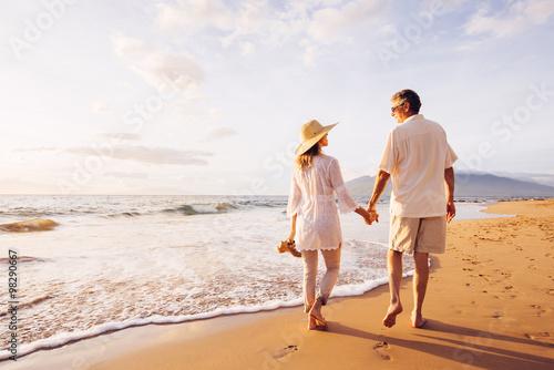 Couple d'âge mûr marcher sur la plage au coucher du soleil Poster