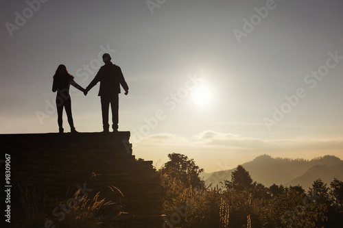 Poster Love couple silhouette looking sunrise in mountains
