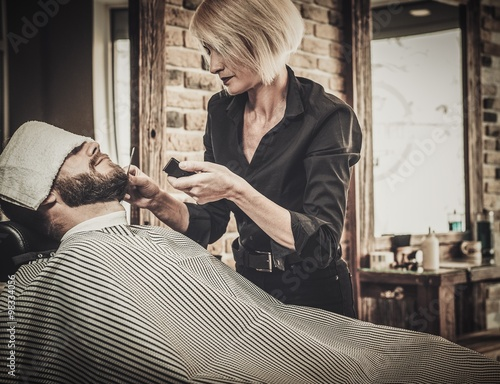 client during beard and moustache grooming in barber shop. Black Bedroom Furniture Sets. Home Design Ideas