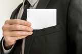 Closeup of businessman removing a blank business card from the p