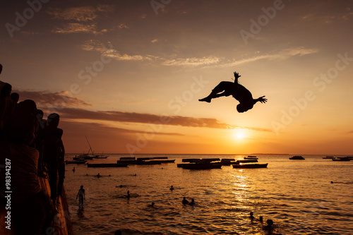 Papiers peints Zanzibar Silhouette of Happy Young boy jumping in water at sunset in Zanz