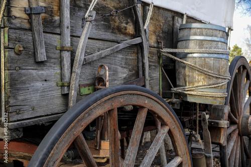 Vue de côté de pionnier wagon avec roue et baril d'eau Poster