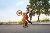 Fototapety Living on the edge. Extreme stunt driver standing on his bike in a stunt soft smudged focus