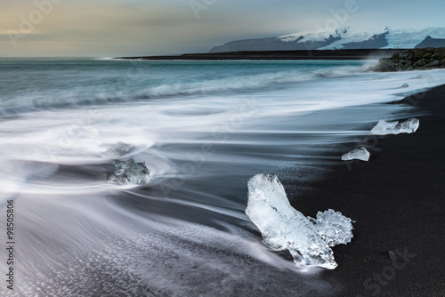 Plakat Ice cube with smooth wave at black sand beach Iceland during sunrise