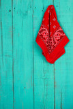 Red bandanna hanging on rustic teal blue background