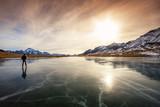 Fototapety lone skater on frozen lake at sunset