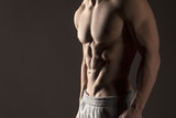 Muscular male torso on a gray background