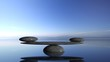 Balancing Zen stones in water with blue sky and peaceful landscape.