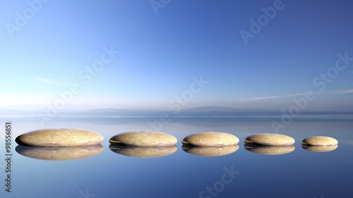 Papiers peints Zen Zen stones row from large to small in water with blue sky and peaceful landscape background.