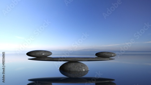 Foto op Canvas Zen Balancing Zen stones in water with blue sky and peaceful landscape.