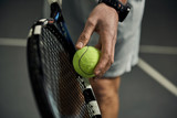 Close-up of male hand holding tennis ball and racket. Professional tennis player starting set.