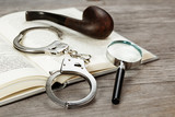 handcuffs, magnifying glass and pipe on book