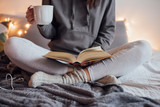 Woman on the bed with book and coffee