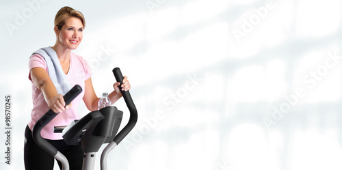 Mature woman doing exercise on elliptical trainer. © Kurhan