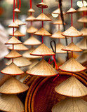 Close up of little Vietnamese hats for sale cascading on strings in Hanoi, Vietnam