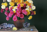 Still life with pink and yellow chrysanthemums in a clay jug and