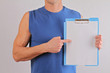 Personal fitness trainer with  workout plan close up. Copy space fitness background