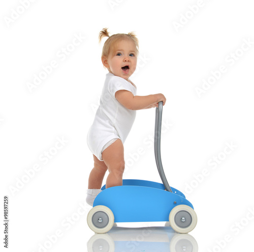 Poster Cute smiling baby girl toddler with toy walker make first steps