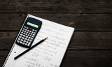 Maths concept - handheld calculator and pencil over a sheet of paper with maths-formulas - 98638682