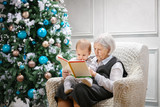 Senior woman reading a book to her great grandson while sitting beside a Christmas tree